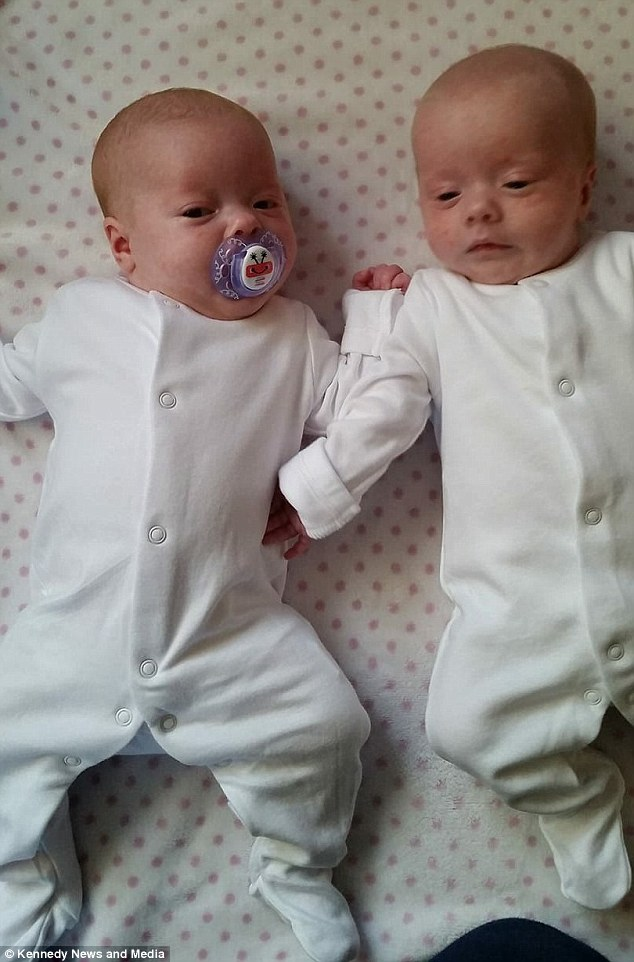 Willow and Freya are seen shortly after birth as they rest in matching white romper suits